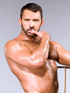 Hunky bear with a beard and barrel chest poses in his leather boots