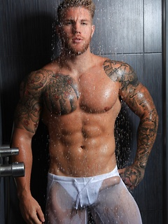 Tattooed dude shows off his big muscles and dick while taking a shower