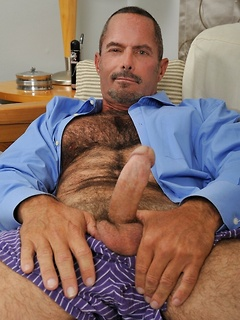 Hunky business daddy strips to show off his hugely hairy chest and stroke his dick
