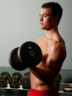 Hot solo hunk in the gym and lifting weights to make his muscles taut and sexy