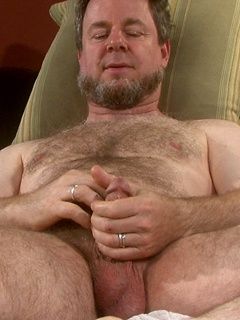 Naughty hairy dude takes off the clothes and plays with his dick on the couch