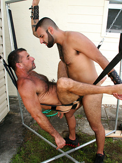 Gay bear puts his ass in a sling and invites a big dick guy to fuck him outdoors