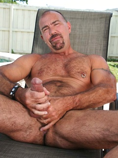 Mature gay guy with a nipple ring strips sitting poolside and jerks off his dick