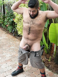 Bear Lanz Adams takes out his cock in the garden and gives it a few strokes